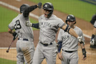 New York Yankees designated hitter Giancarlo Stanton, center, celebrates with teammates after hitting a grand slam home run against the Tampa Bay Rays during the ninth inning in Game one of a baseball American League Division Series Monday, Oct. 5, 2020, in San Diego. (AP Photo/Jae C. Hong)