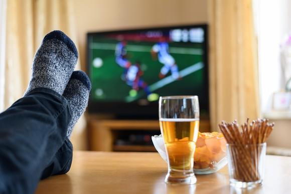 A sports fan watches a soccer match from his couch.
