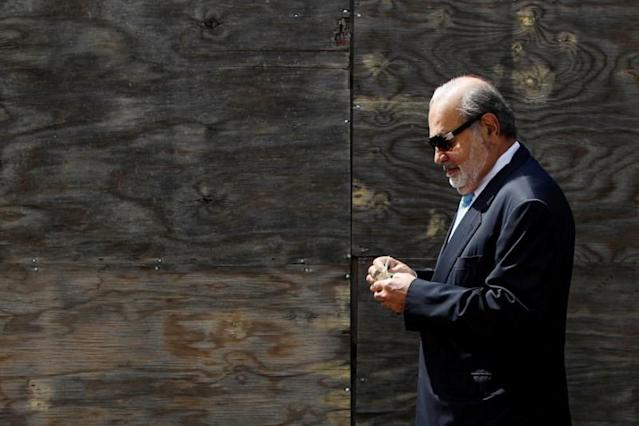 Mexican billionaire Carlos Slim holds money as he walks on a street after attending a ceremony to place the first stone of the new U.S. Embassy, in Mexico City, Mexico, February 13, 2018. REUTERS/Edgard Garrido TPX IMAGES OF THE DAY