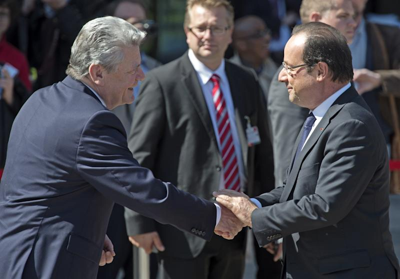 German President Joachim Gauck, left, shakes hands with French President Francois Hollande, right, in Leipzig, Germany, Thursday, May 23, 2013. Germany's main opposition party. the Social Democratic Party, SPD , is celebrating the 150th birthday. The SPD is marking Thursday's anniversary with festivities in Leipzig, the eastern city where it was born in 1863. Guests include its main rival: popular conservative Chancellor Angela Merkel, who's just been named the world's most powerful woman by Forbes magazine for the third consecutive year. (AP Photo/Jens Meyer)
