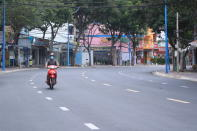 A man rides a scooter on a quiet street in Vung Tau, Vietnam, Sunday, July 18, 2021. Vietnam has put its entire southern region in a two-week lockdown starting midnight Sunday, as confirmed daily COVID-19 cases exceeded 3,000 for the third day in a row. (AP Photo/ Hau Dinh)