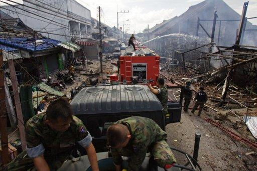Thai members of the security forces gather at the site of a car bomb attack at a packed market in Sai Buri
