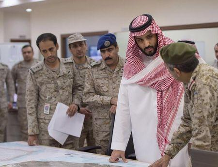 Saudi Defence Minister Prince Mohammad bin Salman is briefed by officers on the military operations in Yemen at the command center in Riyadh, in this March 26, 2015 handout picture. REUTERS/Saudi Press Agency/Handout via Reuters