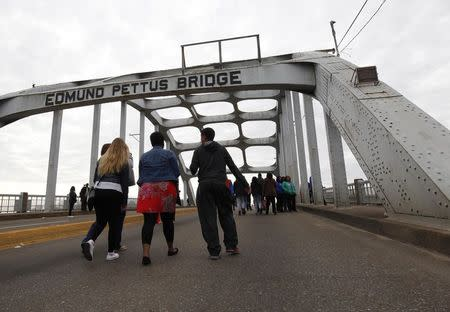 People walk along the Edmund Pettus Bridge before the beginning of the 50th anniversary of the Selma to Montgomery civil rights march in Selma