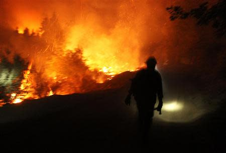 A firefighter uses a headlamp at the Rim Fire at night in this undated United States Forest Service handout photo near Yosemite National Park, California, released to Reuters August 30, 2013. REUTERS/Mike McMillan/U.S. Forest Service/Handout via Reuters