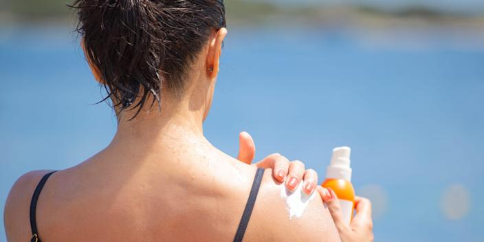A person wearing a tank top applying sunscreen on their right shoulder in front of a lake.