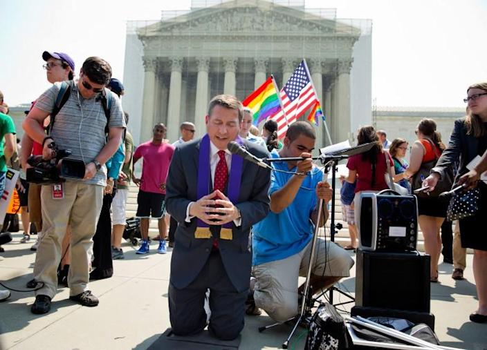 The Rev. Rob Schenck, an opponent of gay marriage, center, prays after the U.S. Supreme Court gave a landmark victory to the gay-rights movement, striking down a federal law that denies benefits to same-sex married couples and clearing the way for weddings to resume in California.