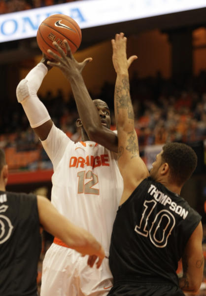 Syracuse's Baye Moussa Keita (12) shoots over High Point's Tarique Thompson, right, in the first half of an NCAA college basketball game in Syracuse, N.Y., Friday, Dec. 20, 2013. (AP Photo/Nick Lisi)