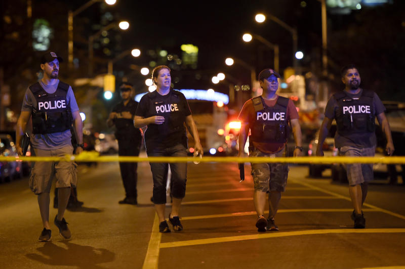Plainclothes police officers work the scene of a shooting in Toronto on Sunday, July 22, 2018. (Nathan Denette/The Canadian Press via AP)