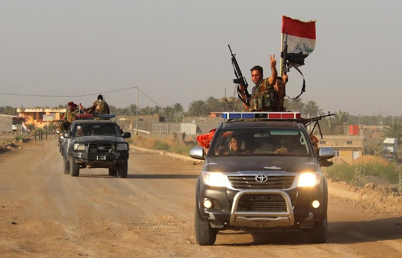 Fighters from the Iraqi pro-government forces flash the sign for victory as they drive vehicles in the Albu Aitha area, north of Ramadi, on May 12, 2016