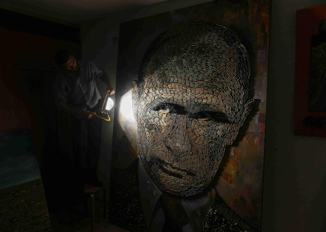 "A portrait of Russian President Vladimir Putin named ""The Face of War"" which is made out of 5,000 cartridges brought from the frontline in eastern Ukraine, is seen in the studio of Ukrainian artist Dariya Marchenko, in Kiev, July 23, 2015. The portrait will be presented along with a novel which will tell personal stories of six people involved in this project including Daria's own story and stories of people who helped her to collect shells from the frontline. Daria Marchenko calls her art approach philosophic symbolism where every element has its hidden meaning. In her works cartridges mean human's life that was brutally ended. Picture taken July 23, 2015. REUTERS/Gleb Garanich"
