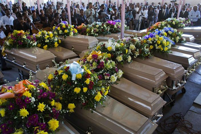 Coffins containing inmates bodies lay inside St. Anne church during the mass burial of inmates who died at the country's largest prison in Port-au-Prince, Haiti. Tuesday Feb. 21, 2017. Relatives wailed in grief or stared stoically as flowers were placed on 20 caskets at a mass funeral for the latest group of inmates who died miserably in Haiti's largest prison, most without ever having been convicted of any crime. ( AP Photo/Dieu Nalio Chery)