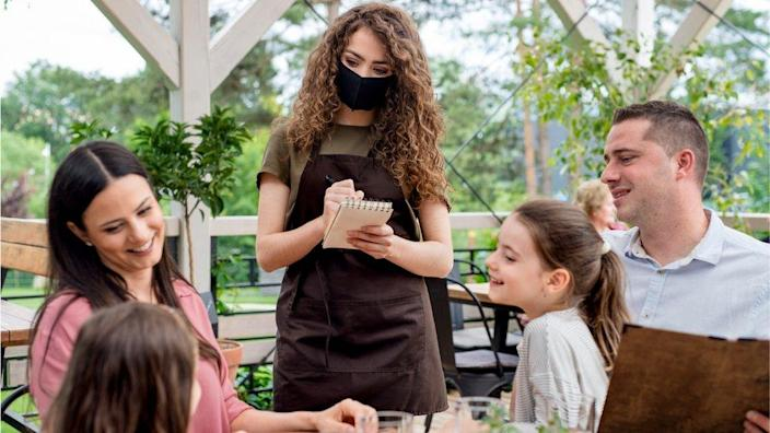Family with waitress in mask