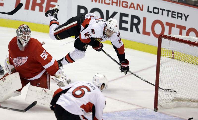 Ottawa Senators left wing Clarke MacArthur (16) passes the puck to right wing Bobby Ryan (6) who scores on Detroit Red Wings goalie Jonas Gustavsson during the third period of an NHL hockey game in Detroit, Wednesday, Oct. 23, 2013. (AP Photo/Carlos Osorio)
