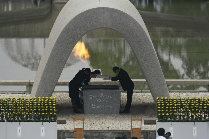 Kazumi Matsui, right, mayor of Hiroshima, and the family of the deceased bow before they place the victims list of the Atomic Bomb at Hiroshima Memorial Cenotaph during the ceremony to mark the 75th anniversary of the bombing at the Hiroshima Peace Memorial Park Thursday, Aug. 6, 2020, in Hiroshima, western Japan. (AP Photo/Eugene Hoshiko)