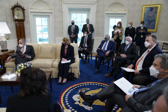 FILE - In this Feb. 3, 2021, file photo President Joe Biden and Vice President Kamala Harris meet with Senate Majority Leader Sen. Chuck Schumer of N.Y., left, and other Democratic lawmakers to discuss a coronavirus relief package, in the Oval Office of the White House in Washington. Biden's push for a giant COVID-19 relief bill is forcing an internal reckoning that pits his instincts to work toward a bipartisan deal against the demands of an urgent crisis and his desire to deliver for those who helped elect him. (AP Photo/Evan Vucci, File)
