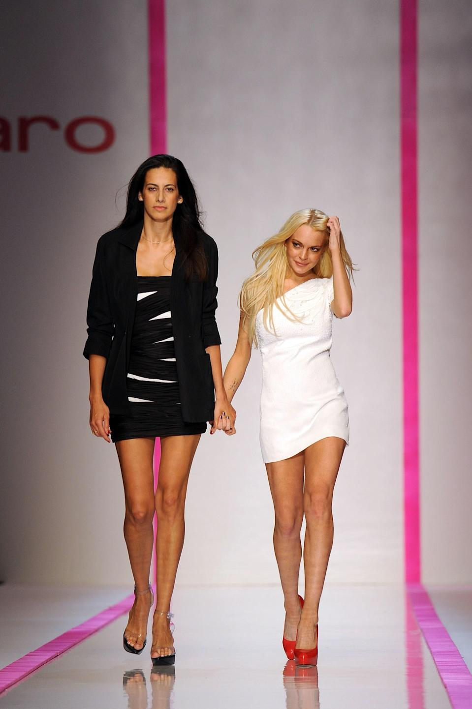"""In 2008, actor Lindsay Lohan launched her leggings line, 6126. In 2009, she then was brought on board as the artistic director of Ungaro along with Estrella Archs. Their <a href=""""https://www.vogue.com/fashion-shows/spring-2010-ready-to-wear/emanuel-ungaro?mbid=synd_yahoo_rss"""" rel=""""nofollow noopener"""" target=""""_blank"""" data-ylk=""""slk:spring 2010 collection"""" class=""""link rapid-noclick-resp"""">spring 2010 collection</a>, filled with bodycon dresses and drop-crotch pants, was panned by critics. Lohan departed the label in 2010."""