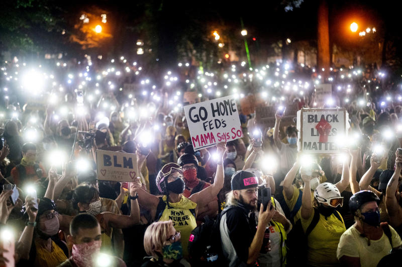 Hundreds of Black Lives Matter protesters hold their phones aloft on Monday, July 20, 2020, in Portland, Ore. Federal officers' actions at protests in Oregon's largest city, hailed by President Donald Trump but done without local consent, are raising the prospect of a constitutional crisis — one that could escalate as weeks of demonstrations find renewed focus in clashes with camouflaged, unidentified agents outside Portland's U.S. courthouse. (AP Photo/Noah Berger)