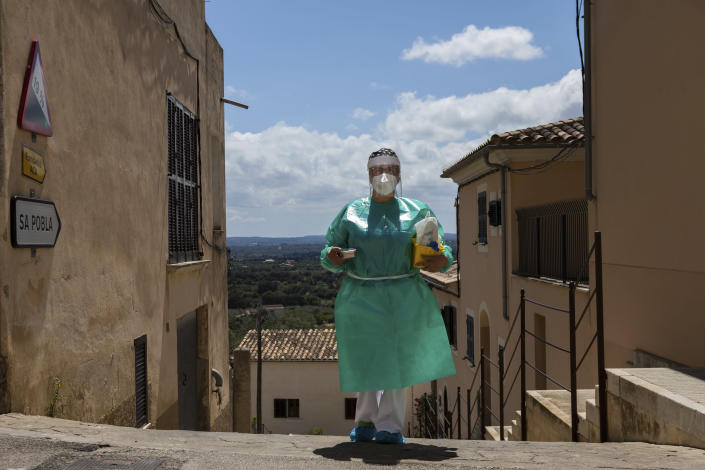 Nurse Pilar Rodríguez arrives at the small town of Buger, barely a thousand inhabitants, at the Spanish Balearic Island of Mallorca, Spain, Friday, April 23, 2021. Pilar Rodríguez, age 49, is one of three nurses in the town of Sa Pobla in the interior of the island to administer shots against COVID-19 there and in nearby villages as Buger.(AP Photo/Francisco Ubilla)