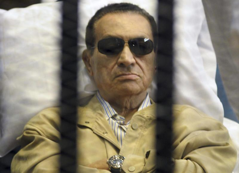 FILE - In this Saturday, June 2, 2012 file photo, Egypt's ex-President Hosni Mubarak lays on a gurney inside a barred cage in the police academy courthouse in Cairo, Egypt. Doctors used a defibrillator twice on Hosni Mubarak when they could not find a pulse Monday, the latest health crisis for the ousted Egyptian president since he was sentenced to life and moved to a prison hospital nine days ago, security officials said. In his last public appearance at his June 2 sentencing, the bedridden Mubarak sat stone-faced in the defendants' cage in the courtroom, his eyes hidden behind dark glasses. Officials said he broke into tears when he learned he was being transferred to a prison. (AP Photo, File)