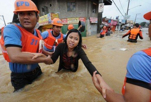 Rescuers help a woman cross a flooded street as residents are evacuated from their homes in the village of Tumana