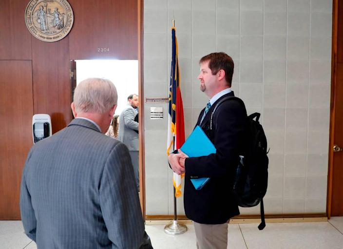 James Alverson, assistant commissioner with the N.C. High School Athletic Association, right, and lobbyist Randolph Cloud wait outside the office on N.C. House Speaker Tim Moore in Raleigh, N.C. Wednesday, July 21, 2021.