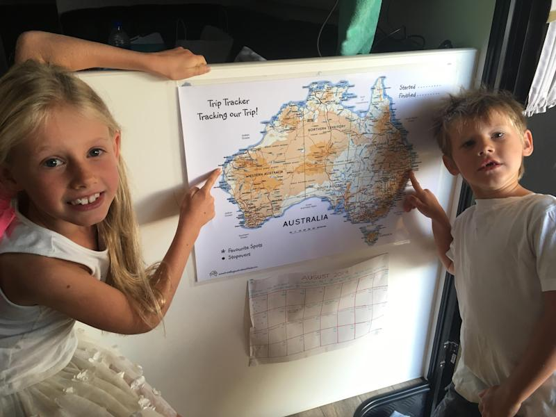 The Pullock children pointing at a map of Australia that charted their 10-month journey.