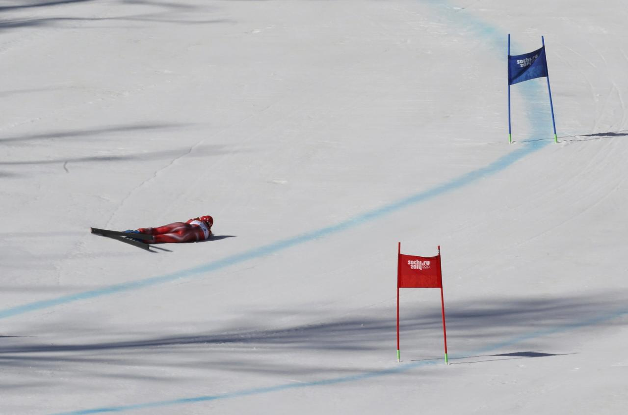 Switzerland's Dominique Gisin lies on the snow after crashing during the women's alpine skiing Super G competition during the 2014 Sochi Winter Olympics at the Rosa Khutor Alpine Center February 15, 2014. REUTERS/Stefano Rellandini (RUSSIA - Tags: SPORT OLYMPICS SPORT SKIING)