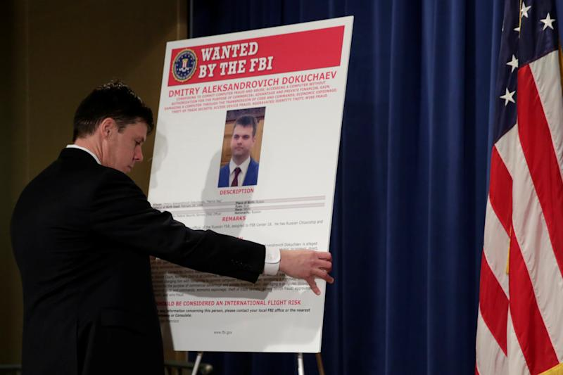 Department of Justice staffer installs a poster of a suspected Russian hacker before FBI National Security Division and the U.S. Attorney's Office for the Northern District of California joint news conference at the Justice Department in Washington, U.S., March 15, 2017. REUTERS/Yuri Gripas