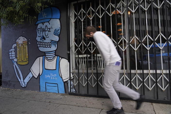 The windows of the closed Baby Blues BBQ restaurant are seen locked in Los Angeles Monday, Jan. 25, 2021. California has lifted regional stay-at-home orders statewide in response to improving coronavirus conditions. Public health officials said Monday that the state will return to a system of county-by-county restrictions intended to stem the spread of the virus. Local officials could choose to continue stricter rules. The state is also lifting a 10 p.m. to 5 a.m. curfew. (AP Photo/Damian Dovarganes)