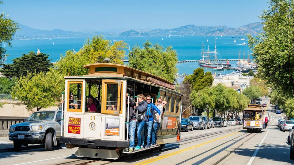 People ride cable car in San Francisco, California, USA on a sunny day.