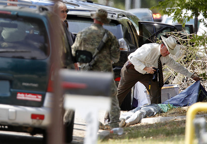 An investigator uncovers a body at the scene where a gunman opened fire on a police officer serving an eviction notice near the Texas A&M University on Monday, Aug. 13, 2012, in College Station, Texas. College Station Assistant Police Chief Scott McCollum says Brazos County Constable Brian Bachmann was among three people, including the gunman, killed in the shootout. (AP Photo/Houston Chronicle, Mayra Beltran) MANDATORY CREDIT: NO SALES, MAGS OUT, TV OUT, INTERNET: AP MEMBERS ONLY