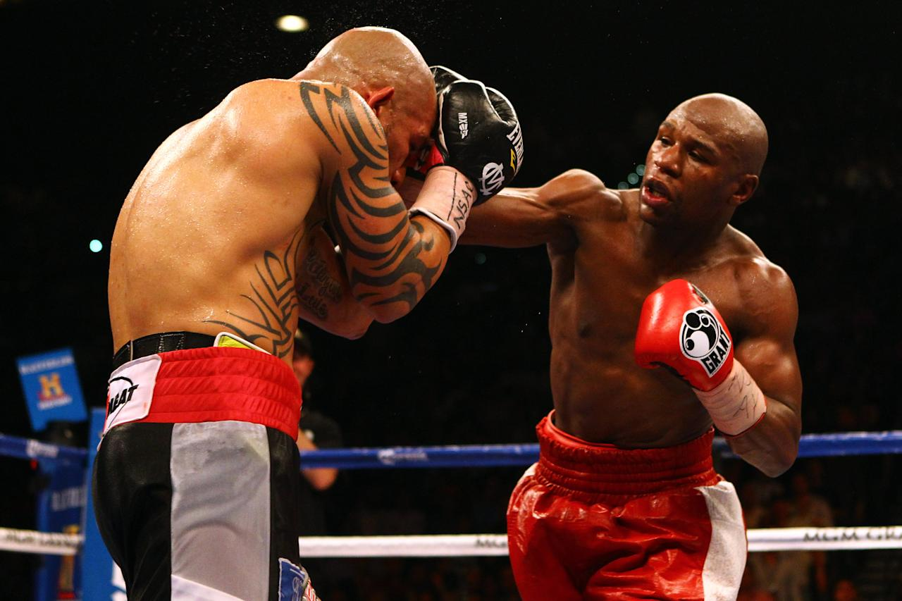 LAS VEGAS, NV - MAY 05:  (R-L) Floyd Mayweather Jr. throws a right to the head of Miguel Cotto during their WBA super welterweight title fight at the MGM Grand Garden Arena on May 5, 2012 in Las Vegas, Nevada.  (Photo by Al Bello/Getty Images)