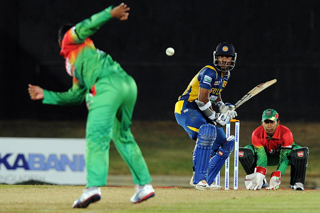 Sri Lankan cricketer Kumar Sangakkara (C) plays a sho as Bangladesh cricket captain Mushfiqur Rahim (R) looks on during the opening one-day international (ODI) match between Sri Lanka and Bangladesh at The Suriyawewa Mahinda Rajapakse International Cricket Stadium in the southern district of Hambantota on March 23, 2013.  Sri Lankan cricket captain Angelo Mathews  won the toss and elected to field. AFP PHOTO/ Ishara S. KODIKARA        (Photo credit should read Ishara S.KODIKARA/AFP/Getty Images)