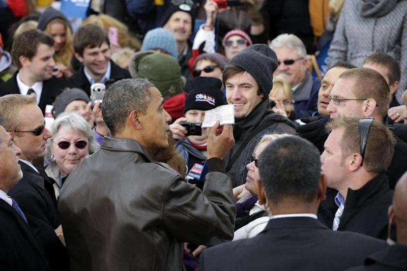 President Barack Obama is handed a personal check made out to the American Red Cross from an unknown supporter during a campaign event at Austin Straubel International Airport in Green Bay, Wis.,Thursday, Nov. 1, 2012. Obama resumed his presidential campaign with travel to key background states of Wisconsin, Colorado, Nevada and Ohio today. (AP Photo/Pablo Martinez Monsivais)