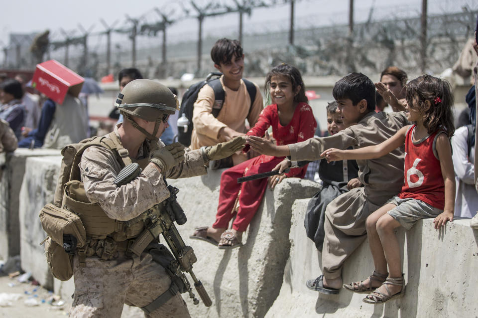 In this image provided by the U.S. Marine Corps, a Marine with Special Purpose Marine Air-Ground Task Force-Crisis Response-Central Command (SPMAGTF-CR-CC) plays with children waiting to process during an evacuation at Hamid Karzai International Airport in Kabul, Afghanistan, Friday, Aug. 20, 2021. (Sgt. Samuel Ruiz/U.S. Marine Corps via AP)