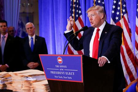 Vice President-elect Mike Pence is seen in the background as U.S. President-elect Donald Trump speaks during a press conference in Trump Tower, Manhattan, New York, U.S., January 11, 2017. REUTERS/Shannon Stapleton