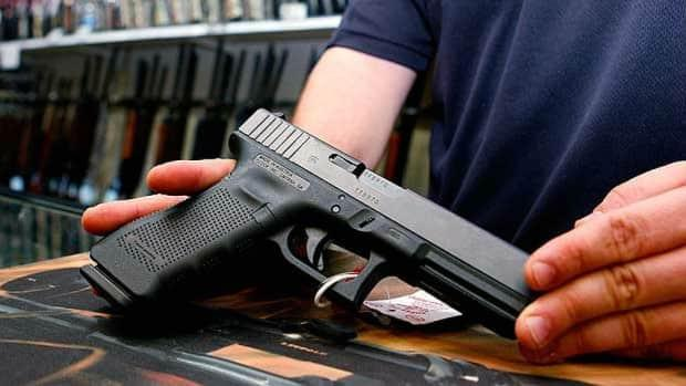 A handgun is displayed by a firearm retailer in this file image. Straw purchasers are people who legally buy weapons for others. (CBC - image credit)