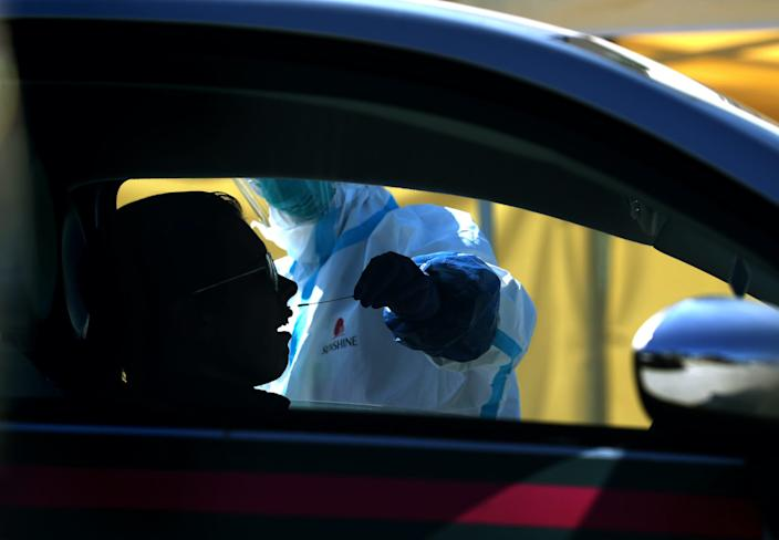 A medical professional administers a coronavirus (COVID-19) test during a drive-thru testing station on March 26, 2020 in Daly City, California.