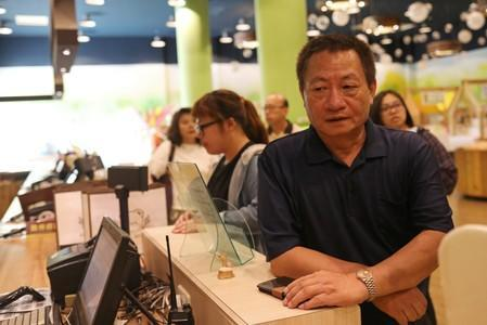 Lin Guo-cing, a senior official of the Chinese Unity Promotion Party, sits at a cashier at a theme park that he is planning to introduce to the China market, in Chiayi