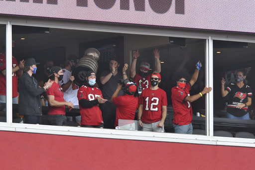 Members of the Tampa Bay Lightning NHL hockey team hold up the Stanley Cup during the first half of an NFL football game between the Tampa Bay Buccaneers and the Los Angeles Chargers Sunday, Oct. 4, 2020, in Tampa, Fla. The Lightning defeated the Dallas Stars earlier this week to win the cup. (AP Photo/Jason Behnken)