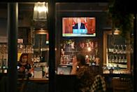 A television shows Britain's Prime Minister Boris Johnson addressing the country on new virus restrictions, as customers sit at the bar inside the William Gladstone pub in Liverpool