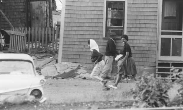 Two young women walk by a house in Africville, N.S., around 1965.