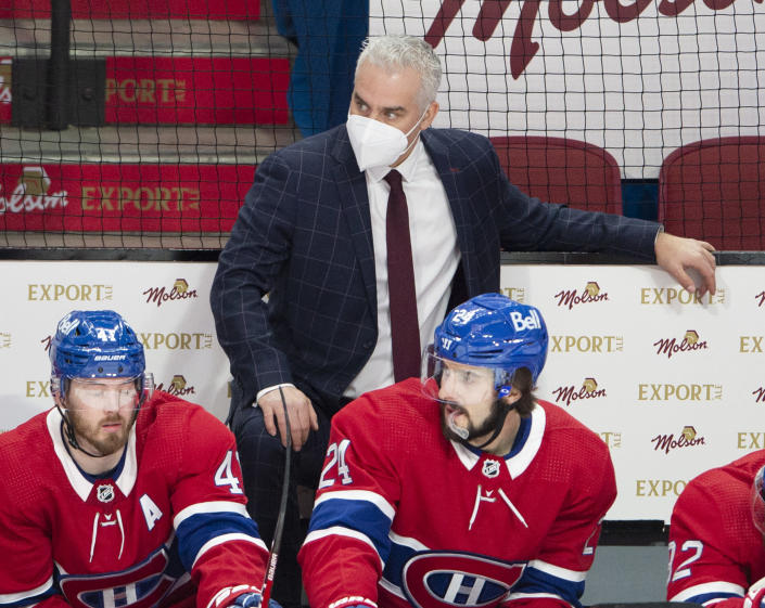 Montreal Canadiens coach Dominique Ducharme keeps an eye on the action, as do Paul Byron (41) and Phillip Danault (24) during the the team's NHL hockey game against the Ottawa Senators on Tuesday, March 2, 2021, in Montreal. (Ryan Remiorz/The Canadian Press via AP)