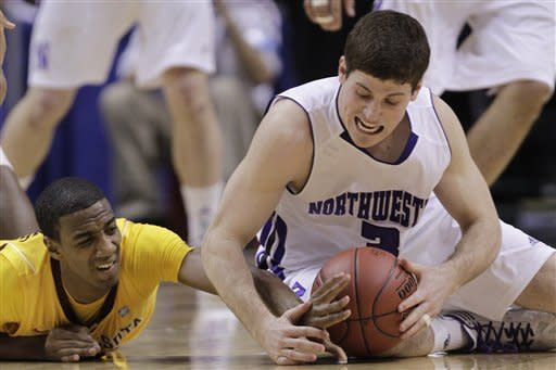 Northwestern guard Dave Sobolewski, right, and Minnesota guard Austin Hollins battle for a loose ball in the first half of an NCAA college basketball game at the first round of the Big Ten Conference tournament in Indianapolis, Thursday, March 8, 2012. (AP Photo/Michael Conroy)