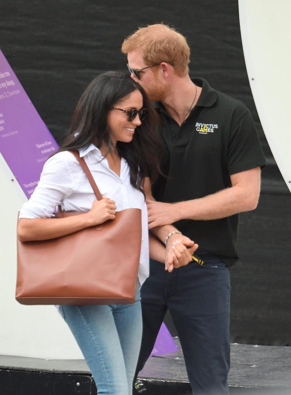 Prince Harry and Meghan Markle in 2017. Harry kisses Meghan on the forehead.