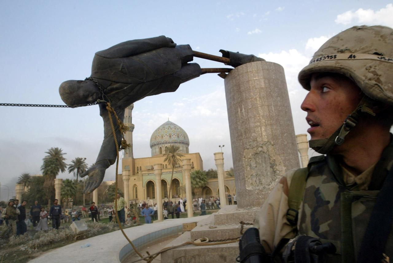 A U.S. soldier watches as a statue of Iraq's President Saddam Hussein falls in central Baghdad April 9, 2003. U.S. troops pulled down a 20-foot (six metre) high statue of President Saddam Hussein in central Baghdad on Wednesday and Iraqis danced on it in contempt for the man who ruled them with an iron grip for 24 years. [In scenes reminiscent of the fall of the Berlin Wall in 1989, Iraqis earlier took a sledgehammer to the marble plinth under the statue of Saddam. Youths had placed a noose around the statue's neck and attached the rope to a U.S. armoured recovery vehicle.]