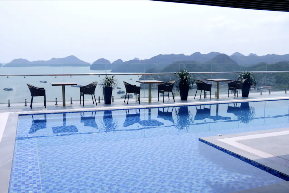 Large rooftop pool with seating that overlooks the karsts of Halong Bay