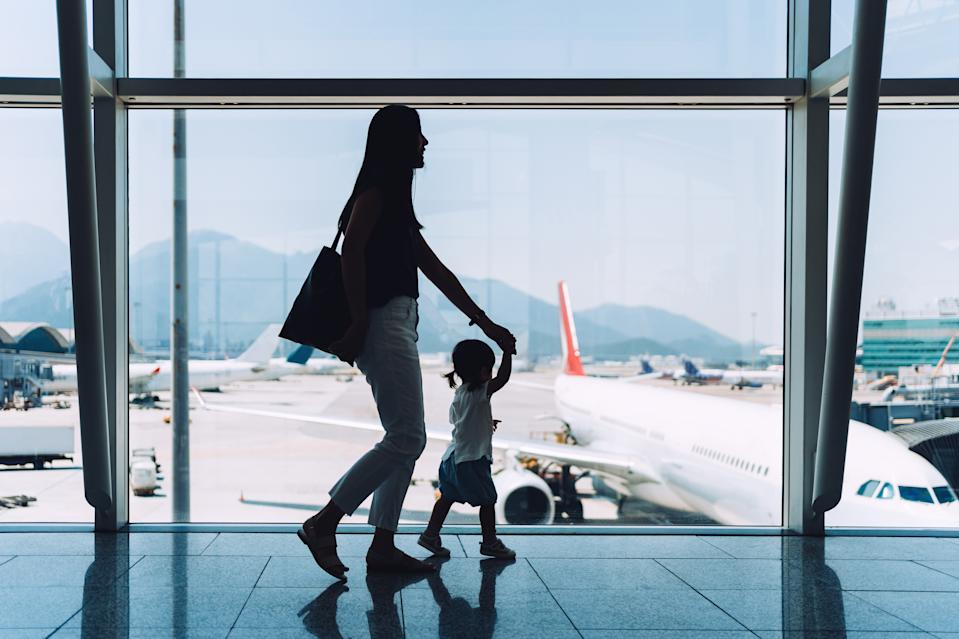 Silhouette of joyful young Asian mother holding hands of cute little daughter looking at airplane through window at the airport while waiting for departure