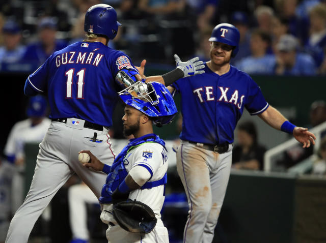 Texas Rangers' Ronald Guzman (11) celebrates his two-run home run with teammate Logan Forsythe, right, during the sixth inning of a baseball game against the Kansas City Royals at Kauffman Stadium in Kansas City, Mo., Wednesday, May 15, 2019. Kansas City Royals catcher Martin Maldonado, front, handles a new ball. (AP Photo/Orlin Wagner)